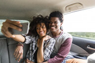 Happy couple taking selfie while traveling in car - CAVF49729