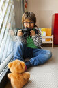 Portrait of boy photographing teddy bear while sitting at home - CAVF49738