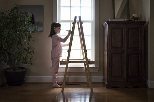 Side view of girl drawing on artist's canvas at home - CAVF49789