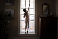 Rear view of girl in ballet costume closing window at home - CAVF49792