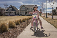 Happy girl riding bicycle on road against sky during sunny day - CAVF49795