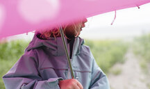 Midsection of girl carrying umbrella while standing outdoors during rainy season - CAVF49813