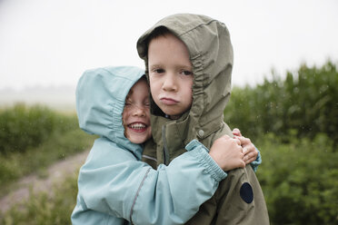 Portrait of sad brother being embraced by happy sister while standing against plants during rainy season - CAVF49816
