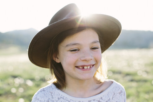 Close-up of happy girl wearing hat while standing against sky during sunny day - CAVF49825