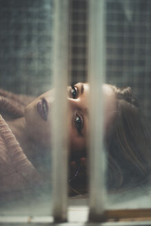 Close-up portrait of woman looking through window while lying on tile - CAVF49846