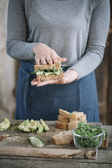 Midsection of woman making sandwich on wooden table at home - CAVF49852