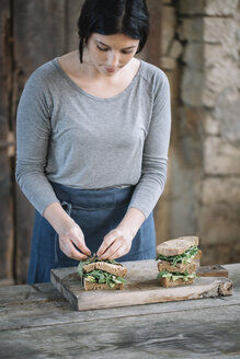 Woman making sandwich on cutting board at home - CAVF49855