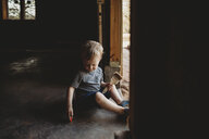 Baby boy with brush sitting at entrance in abandoned room - CAVF49864
