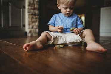 Cute baby boy eating cookie while sitting on floor at home - CAVF49870