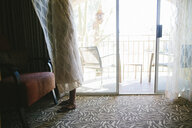 Playful girl wrapping in curtain while hiding at home - CAVF49876
