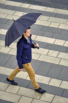High angle view of young businessman with umbrella walking on sidewalk in city during rainfall - CAVF49897
