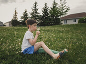 Side view of boy with broken leg blowing dandelion while sitting on grassy field at park - CAVF49909