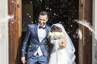 Confetti throwing on happy newlywed couple standing at church entrance - CAVF49912