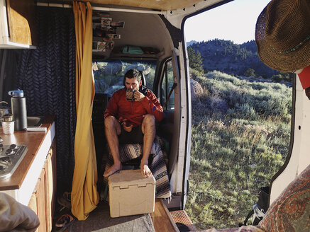Man having drink while sitting in motor home at forest - CAVF49915