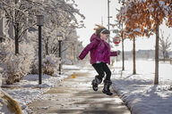 Happy girl jumping on road against sky during winter - CAVF49927