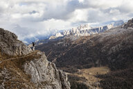 Female hiker standing on mountain against cloudy sky - CAVF49936