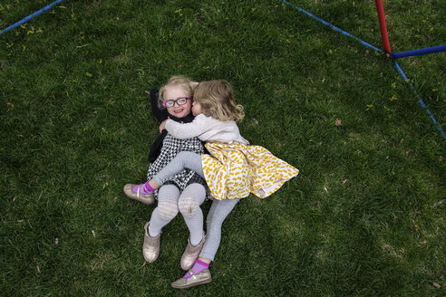 High angle view of happy sisters lying on grassy field at yard - CAVF49954