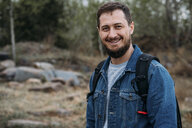 Portrait of smiling man with backpack wearing denim jacket in nature - VPIF00917