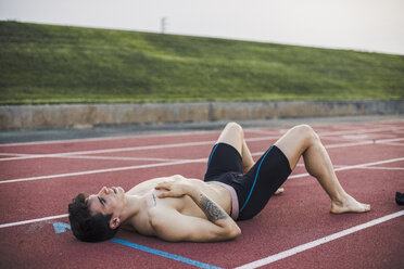 Athlete lying resting on a tartan track after finishing a race - ACPF00361