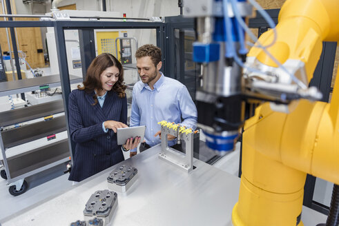 Colleagues in high tech company controlling industrial robots, using digital tablet - DIGF05146