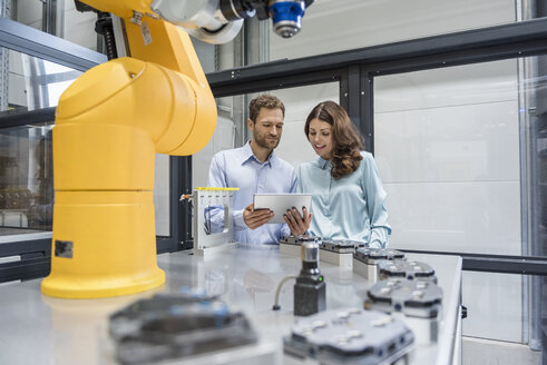 Colleagues in high tech company controlling industrial robots, using digital tablet - DIGF05155