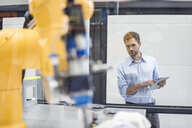 Businessman checking industrial robot in high tech company - DIGF05173