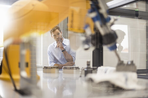 Businessman checking industrial robot in high tech company - DIGF05176