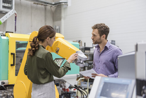 Businessman and woman having a meeting in front of industrial robots in a high tech company - DIGF05227