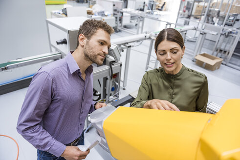 Businessman and woman having a meeting in front of industrial robots in a high tech company - DIGF05230
