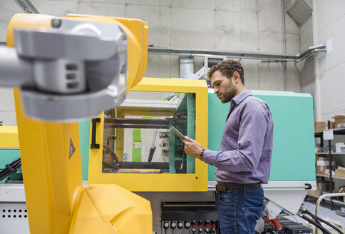 Businessman checking industrial robot in high tech company - DIGF05233