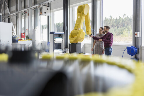 Businessman and woman having a meeting in front of industrial robots in a high tech company - DIGF05254