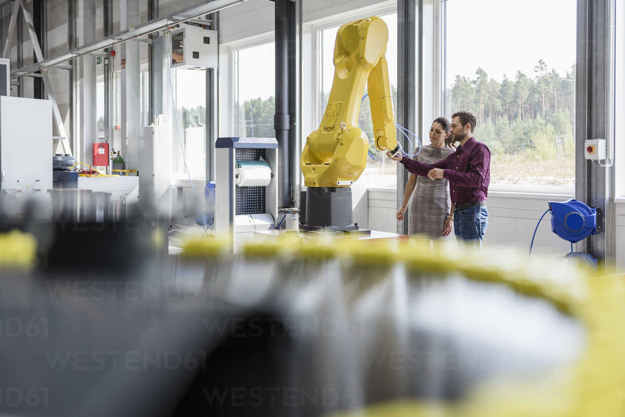 Businessman and woman having a meeting in front of industrial robots in a high tech company - DIGF05254 - Daniel Ingold/Westend61