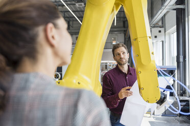 Businessman and woman having a meeting in front of industrial robots in a high tech company - DIGF05257