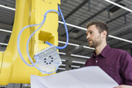 Businessman checking industrial robot in high tech company - DIGF05260