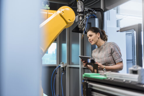 Businesswoman checking industrial robot in high tech company - DIGF05263