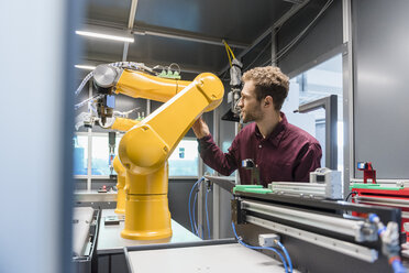 Businessman checking industrial robot in high tech company - DIGF05266