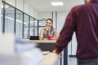 Female employee sitting at desk, talking to colleague - DIGF05272