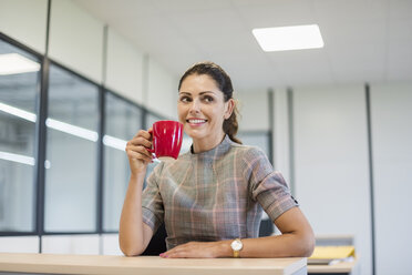 Pretty office worker sitting at desk with red coffee cup - DIGF05275