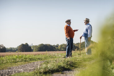 Two old friends standing in the fields, talking about old times - UUF15451