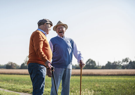 Two old friends standing in the fields, talking about old times - UUF15454