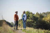 Two old friends standing in the fields, talking about old times - UUF15460