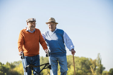 Old friends taking a stroll in the fields with walking stick and wheeled walker, talking about old times - UUF15490