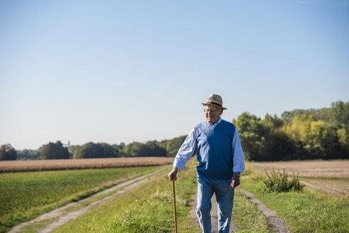Senior man with a walking stick, walking in the fields - UUF15499
