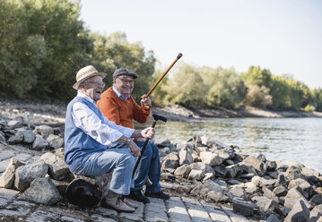 Two old friends sitting by the riverside, having fun - UUF15502