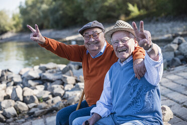 Two old friends sitting by the riverside, having fun - UUF15505