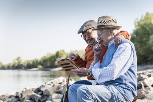 Two old friends sitting by the riverside, using digital tablet - UUF15508