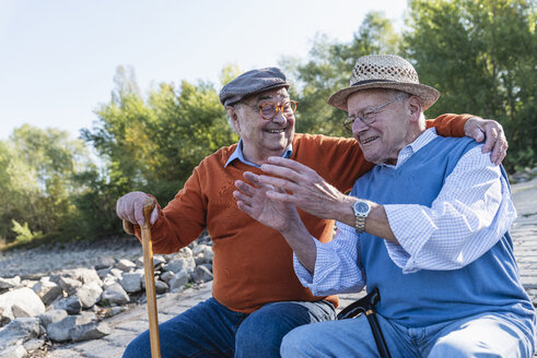 Two old friends sitting by the riverside, having fun - UUF15511