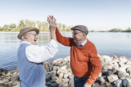 Two laughing old friends high-fiving at a lake - UUF15514