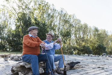 Two old friends sitting on a tree trunk by the riverside, sharing memories - UUF15523
