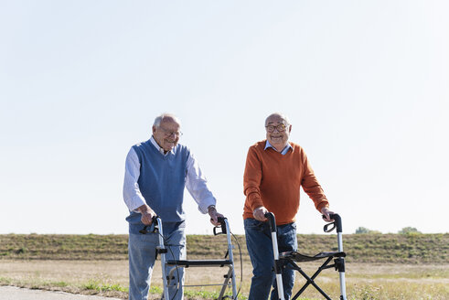 Two old friends walking on a country road, using wheeled walkers - UUF15526